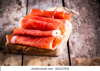 thin slices of prosciutto on wooden cutting board
