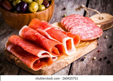thin slices of prosciutto  with salami and olives on wooden cutting board