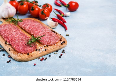 Thin slices of salami on a wooden board with spices and vegetables. Selective focus.