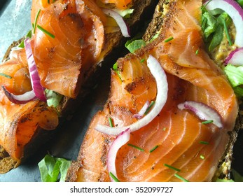 Thin slices of salmon on dark bread with onion and chives