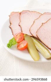 Thin slices of smoked pork roast  on white plate