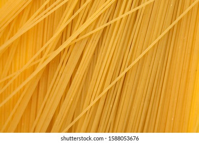Thin spaghetti background top view. Uncooked raw spaghetti.