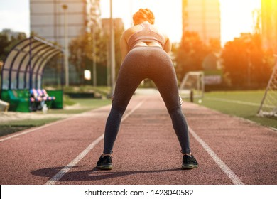 Thin Sportive Girl Bent Over Turned Back to Camera. Blond Young Female Sportsman Doing Stretching Exercises. Athlerthic Road Background.