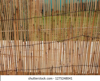 Thin sticks of bamboo tied together for fencing.