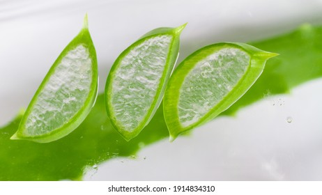Thin transparent slices of green aloe vera leaf in drops of water and juice on a transparent background