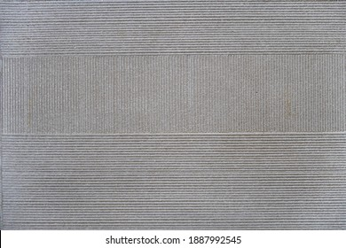 Thin vertical and horizontal grooves on a flat ceramic surface, background