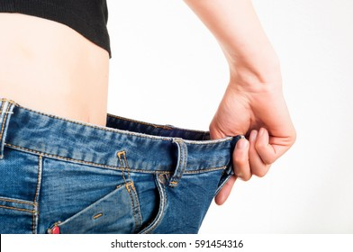 Thin white woman wearing loose jeans. White background. Exercise and weight loss concept
