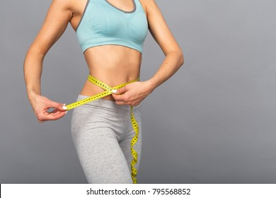 Thin woman measure her waist using the measure tape.