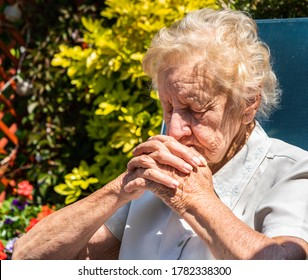 Thin wrinkled old lady, with curly grey blond hair, takes a nap in the garden while sitting in the sunshine. Her eyes are closed and her hands folded together, fingers interlocked, against her chin.