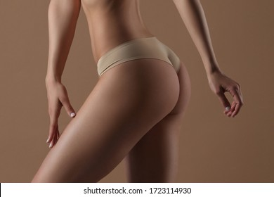 Thin young woman woman strokes her thigh on beige background. Side view. Fitness, diet, skin and body care