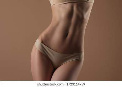 Thin young woman in underwear on beige background. Fitness, diet, skin and body care