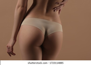 Thin young woman in underwear on beige background. Back view. Fitness, diet, skin and body care