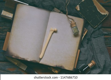 Things hunter for evil, demons, vampires and zombies - an old notebook, a book with spells, a knife, flask of holy water, pen bone, alcohol, a cross. Men's accessories on a dark background.