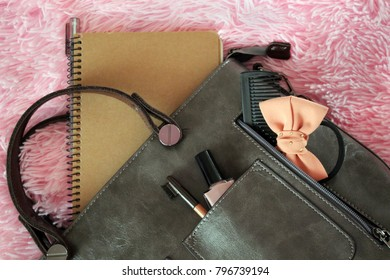 Things from open lady handbag. Cosmetics and women's accessories fell out of the gray handbag on pink veil background. Toned image.