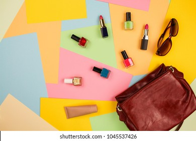 Things from open lady purse. Cosmetics and women's accessories fell out of blue handbag on colourful background. Top view.