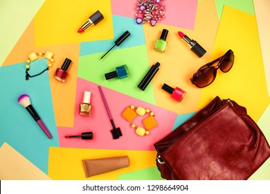 Things from open lady purse. Cosmetics and women's accessories fell out of red handbag on colourful background. Top view. Flat lay.