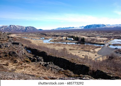 Thingvellir, famous destination of the golden circle tour in southwest Iceland, view of the faraway chapel and oldest parliament, crack and river, snow-capped mountain backdrop on sunny and blue sky