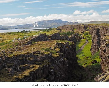 Thingvellir national park Iceland - north american - europe lithospheric rift - Mid-Atlantic Ridge with path and walking people and lake and mountain behind