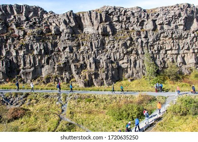 THINGVELLIR NATIONAL PARK, ICELAND - SEPTEMBER 19, 2018: Tourists walk on pathway. The park lies in a rift valley between the North American and Eurasian tectonic plates. Golden Circle South Iceland.