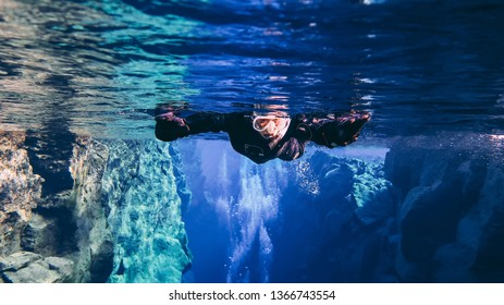 Thingvellir, Silfra / Iceland - April 5th 2019: Snorkelers and scuba divers swimming in famous popular fissure drift with blue crystal clear glacial water between tectonic plates mid atlantic ridge