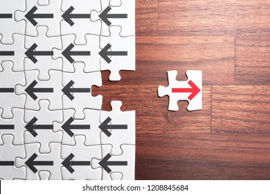 Think different, unique and courage to go alone concept. Jigsaw puzzle piece with red arrow facing the opposite direction from crowd.