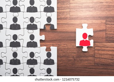 Think different, unique and courage to go alone concept. Jigsaw puzzle piece with red businessperson facing the opposite direction from crowd.
