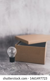 think outside the box concept: open box with miniature lightbulbs inside and a unique one outside on a spring