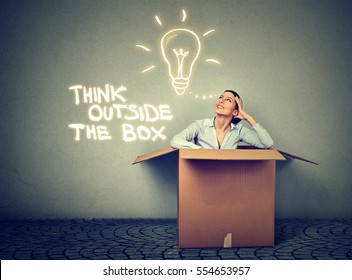 Think outside the box concept. Young woman coming out of box with great bright idea light bulb isolated on gray wall background