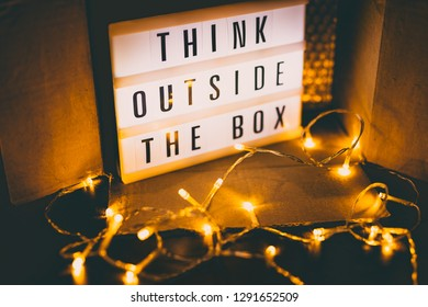 Think outside the box message on lightbox next to open parcel with fairy led lights, concept of being unique for success