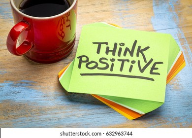 think positive - inspirational handwriting in a green sticky note with a cup of coffee