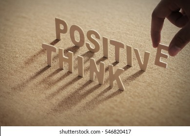THINK POSITIVE wood word on compressed or cork board with human's finger at E letter.