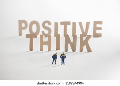 THINK POSITIVE word  with Miniature people: Engineer standing infront use as business concept.
