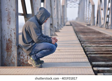 Thinker teenager in depression sitting down on the bridge at the sunset. Concept of teenage problems. Unhealthy habits