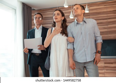Thinking about buying. Couple standing in the room thinking about buying house after listening to realtor
