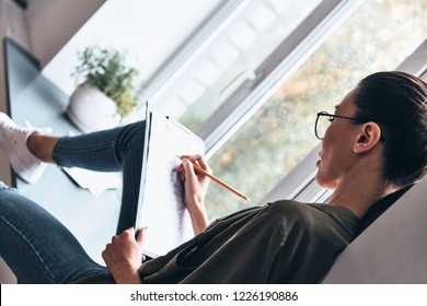 Thinking about every detail. Top view of concentrated young woman writing something down while sitting on the window sill in the office
