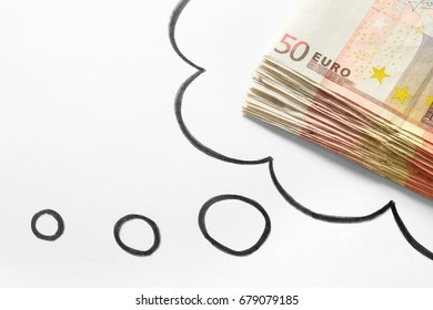 Thinking about money. Dreaming of rich and wealthy life. Money on mind. Lucrative new business idea. Hand drawn thinking speech bubble and thought cloud and a stack of 50 euro bills.