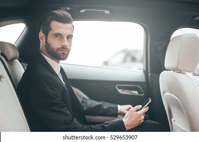 Thinking about new possibilities. Confident young businessman setting his smart phone and looking at camera while sitting in the car