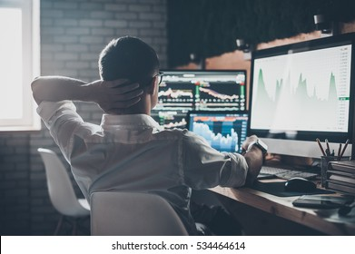 Thinking about new solutions. Rear view of young man in casual wear holding hand on the back of the head and working while sitting at the desk in creative office
