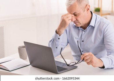 Thinking About Problems. Fatigued senior businessman massaging nosebridge with closed eyes, free space