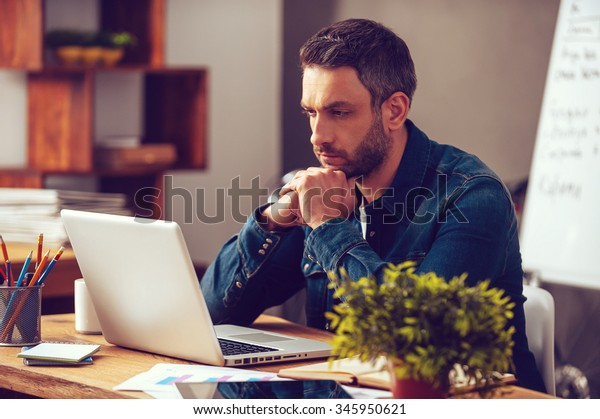 Thinking about solution. Concentrated young man looking at his laptop while sitting at his working place in office