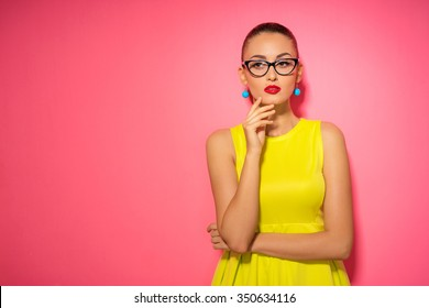 Thinking about solutions. Colorful studio portrait of thoughtful young woman in yellow dress holding hand on chin against pink wall.