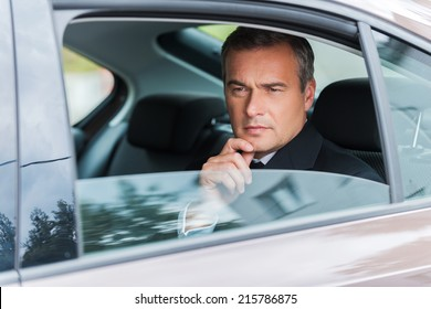 Thinking about solutions. Thoughtful mature businessman holding hand on chin and looking away while sitting on the back seat of a car