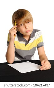 Thinking About What to Write. Elementary school student sitting in front of a blank piece of paper, appearing to think about what he is going to write. Isolated on white.