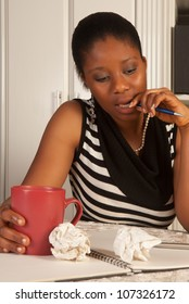 Thinking african woman writing a letter at home