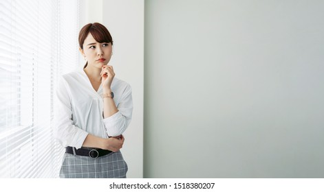 Thinking asian woman in office.,