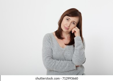 Thinking attractive middle aged brunette woman with folded arms on grey background. Menopause and health care.