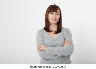 Thinking attractive middle aged woman with folded arms on grey background. Menopause and health care.
