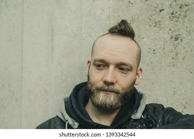 thinking bearded man looking down in front of a wall