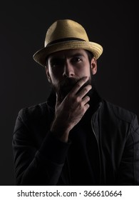 Thinking bearded man wearing straw hat touching beard looking at camera. Low key dark shadow portrait over black background.