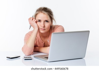 thinking beautiful blond girl leaning her head and lying on her white sparse desk, studying or working hard on her computer, isolated white background